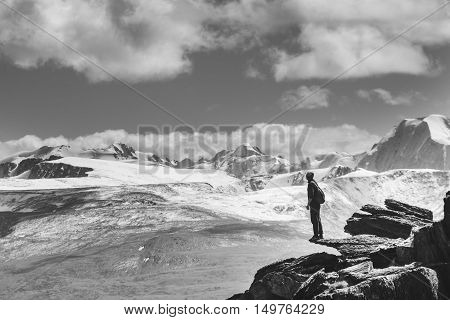 Concept photo. Man stands on the cliff and looks on the mountains.
