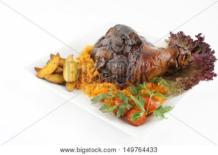 Fried pork knuckle with potatoes and tomato. Isolated