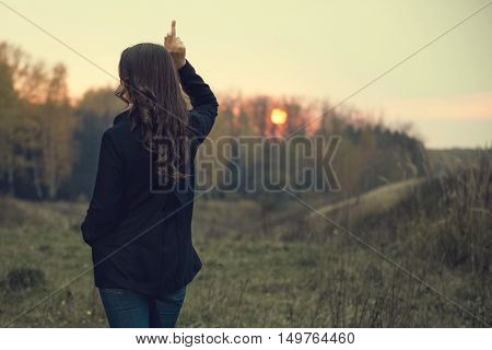 Portrait of a woman outdoors. Photo from behind. A girl showing middle finger