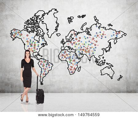 Smiling buisnesswoman in black is standing with her suitcase near concrete wall with world map and landmarks. Concept of international flights.