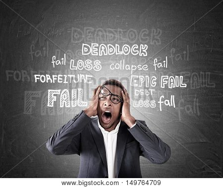 Overwhelmed African American businessman shouting in despair near chalkboard with failure words. Concept of losing it and stress at work.
