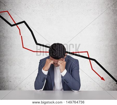 Portrait of stressed out Asian businessman sitting against concrete wall with declining graphs of it. Concept of economical crisis