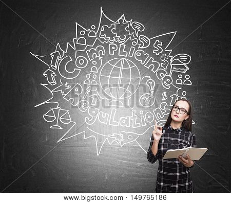 Nerd girl in dress holding a book and standing near the blackboard with bureaucracy sketch on it. Concept of rules and regulations.