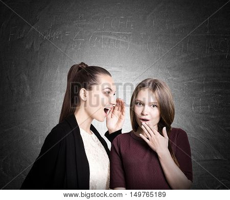 Two college students in casual clothes are gossiping near blackboard. Concept of rumor circulation. Mock up