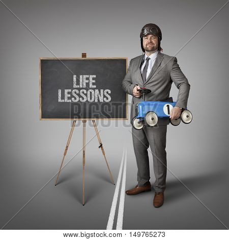 Life lessons text on blackboard with businessman and toy car