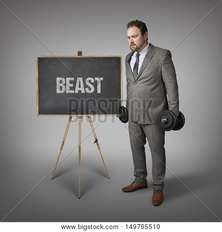 Beast text on blackboard with businesssman holding weights