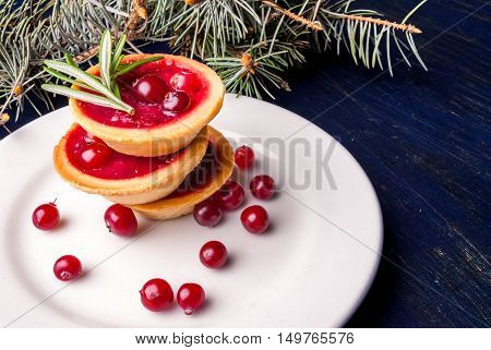 Winter one bite-sized snack or dessert: tartlets with sweet and sour cranberry sauce, decorated with rosemary. copy space