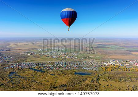 Hot air balloon flying over rural landscape at autumn day. Kaskara. Tyumen region. Russia