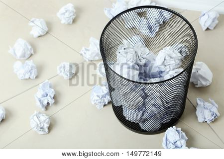 Office trashcan with crumpled paper balls, close up