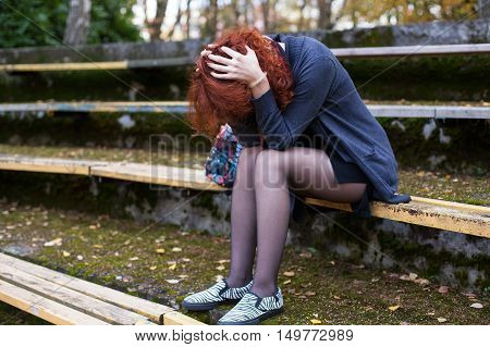 Crying woman sitting on the bench face is hidden by the hair head down in the hands