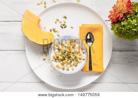 Porridge with pumpkin and milk on a white plate