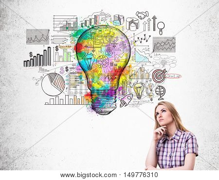 Blond girl in checkered shirt and startup sketch with colorful light bulb. Concept of idea for business.