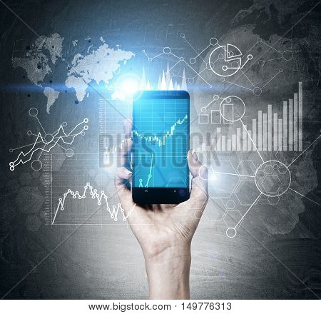 Man's hand holding smartphone with graphs on screen. Diagrams and world map are on blackboard in the background. Toned image.