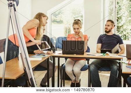 Teaching helping technology concept. Woman young teacher or tutor with adult students in classroom at desk with papers laptop computer. Studies course