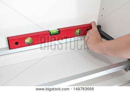 The assembly of kitchen furniture carpenter measuring the level with special tool close-up of worker hands holding red building level.