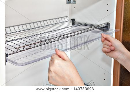 Installing shelf under kitchen cupboard with inside wire plate rack close-up of a woman hands holds drip tray.