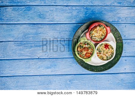 Scrambled eggs baked with fillings in mini ceramic forms and plate