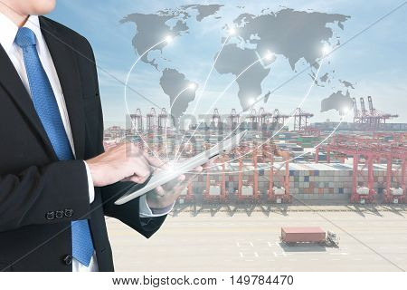 Import Export Logistics concept - Businessman press digital tablet to show global network partnership connection use for logistic import export background.(Elements of this image furnished by NASA)