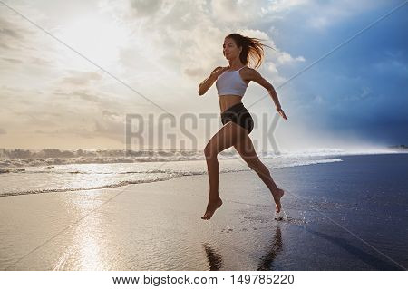 Active sporty woman run along ocean surf by water pool to keep fit and health. Sunset black sand beach background with sun. Woman fitness morning workout and sport activity on summer family holiday.
