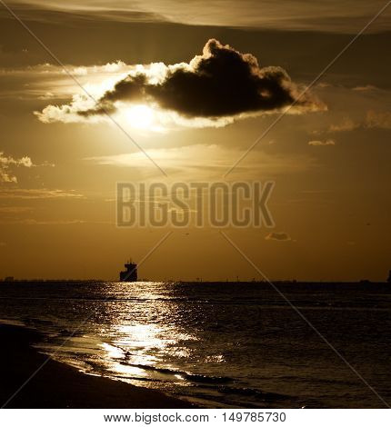 Boat at sunset in the ocean, sun blocked by cloud