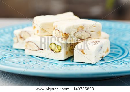 pieces of white nougat served on a blue plate.