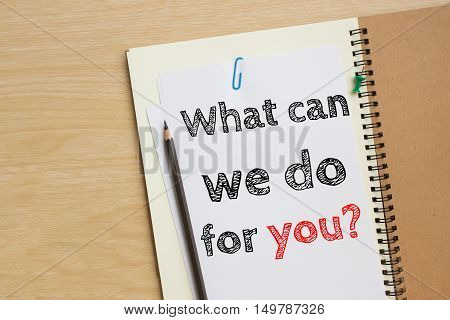 Text what can we do for you on white paper and pencil / business concept