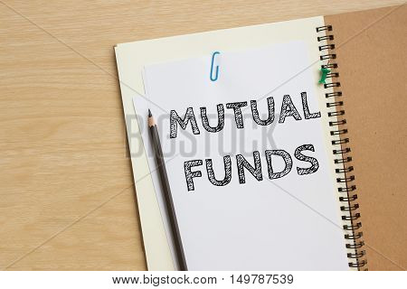 mutual funds text message on white paper note on the desk / business concept