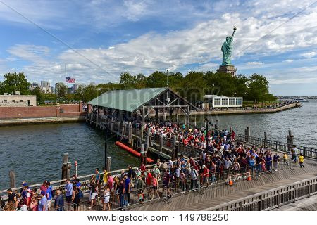 New York City - September 11 2016: The Statue of Liberty from Liberty Harbor with a crowd of tourists awaiting to take a boat to Ellis Island.
