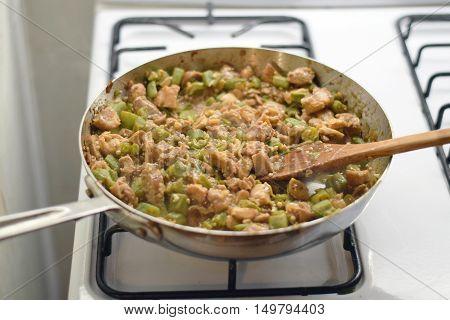 Wooden spatula stirring frango com quiabo (Portuguese for