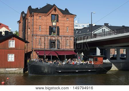 PORVOO, FINLAND - JUNE 13, 2015: Summer dining on the deck of an old barge in the old part of Porvoo. Tourist landmark of the city Porvoo, Finland