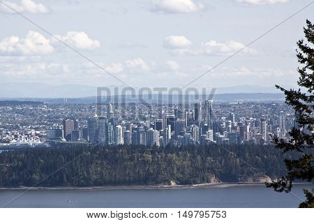 View of downtown Vancouver from atop Cypress Bowl Drive in West Vancouver BC looking across Burrard Inlet and past Stanley Park and into the city on a beautiful bright sunny day in April. A single fir tree on the right.