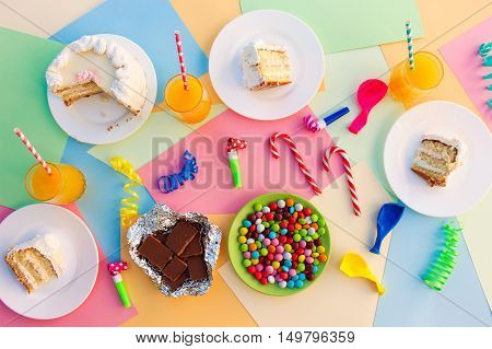 Cake, candy, chocolate, whistles, streamers, balloons, juice on holiday table. Concept of children's birthday party. View top.