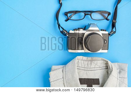 Top view of men lifestyle items - vintage camera eyeglasses and shirt on blue background