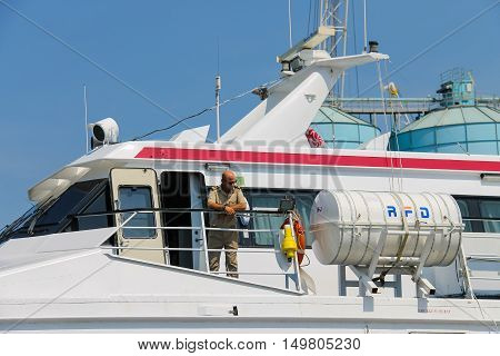 Piombino Italy - June 30 2015: Man on the deck of ferry boat Marmorica at berth in the seaport