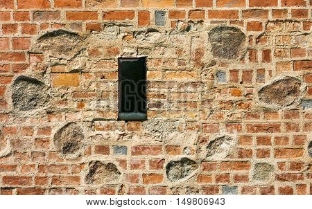 outdated medieval window in horizontal composition with old wall stone