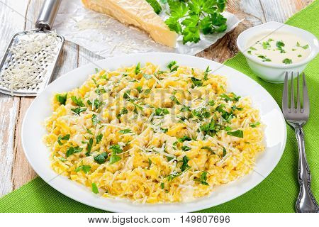 Fettuccine Alfredo served in a sauce of cream butter and grated Parmesan cheese sprinkled with parsley on white dish on old peeling paint planks view from above authentic italian recipeclose-up