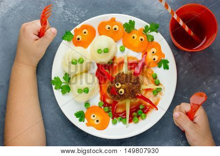 Creative idea for baby dinner or lunch. Funny spider meatball with colorful vegetables garnish shaped ghosts and carrot pumpkins. Concept of healthy meal food for children top view