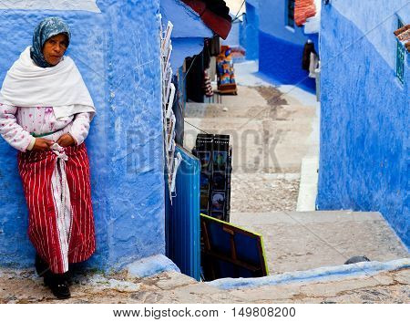 CHEFCHAOUEN, MOROCCO - JANUARY 2, 2014: Muslim women standing on the street in ancient blue Medina in Chefchaouen city.
