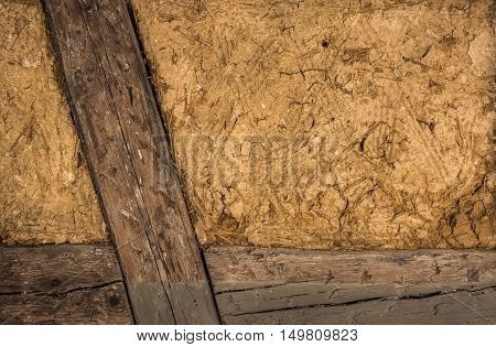 House wall with wood frame and clay - Clay house wall with details on the wooden beams and the mixture of mud and straw perfect as background