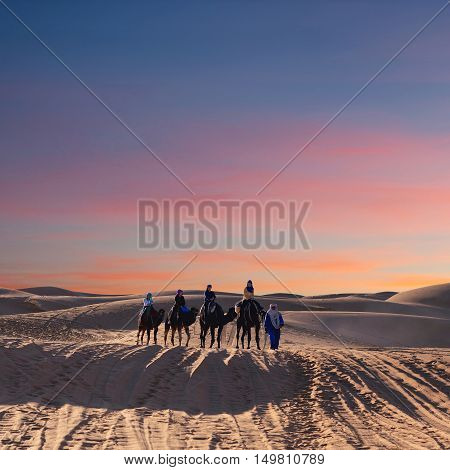 ERG CHEBBI, MOROCCO - JANUARY 6, 2014: Caravan crossing over dunes in desert in Western Sahara. Tourism is an important item in the economy of Morocco