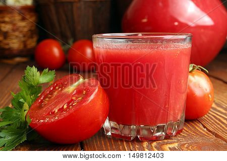 Glass of tomato juice and fresh tomatoes on old wooden table