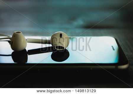 close up headphone stack on phone in black color tone new headphone modern design device of phone technology