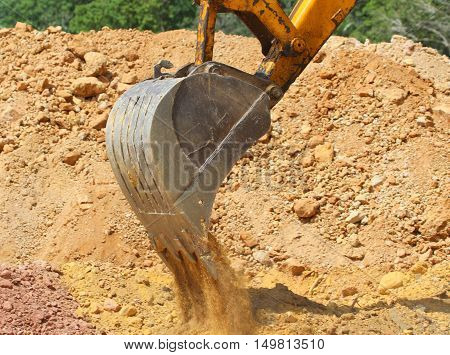 excavation power bucket dumping out dirt onto a pile, construction site near Songkhla, Thailand