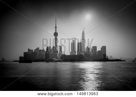 Shanghai sunrise silhouette with Oriental Pearl Tower Huangpu River Pudong district Shanghai China. Black and White Long exposure with ND Grad filter visible noise.