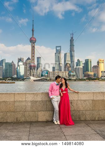 Shanghai China - October 26 2013: Chinese couple at the Bund and modern city skyline. It is a waterfront area central Shanghai which runs along the western bank of Huangpu River facing Pudong skyscrapers Shanghai China.