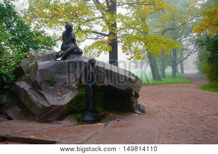 Foggy morning in the Catherine park in Tsarskoye Selo. Girl with a jug