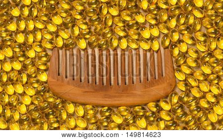 Wooden hair comb with yellow pills and nutritional supplements as a background. Beauty haircare concept, closeup, top view.