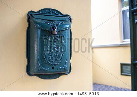 Mailbox hangs on beige wall. Personal iron mailbox. Mail offline.