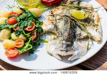Fresh fish sea bream bream with salt herbs and pepper prepares grilled.
