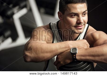Pleasant workout. Good looking joyful optimistic sportsman leaning on a dumbbell and smiling while working out